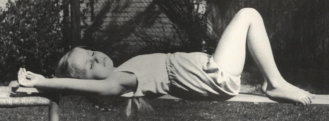 Mädchen, auf dem Rücken liegend, auf Holzbrett, in völliger Entspannung
